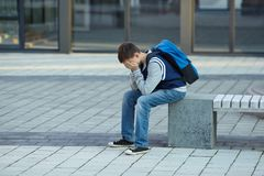Schoolboy crying in the yard of the school stock image