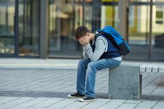 Schoolboy crying in the yard of the school royalty free stock images