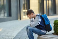 Schoolboy crying in the yard of the school royalty free stock photography