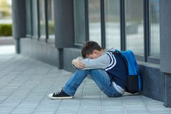 Schoolboy crying in the yard of the school royalty free stock photo