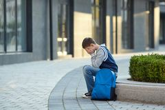 Schoolboy crying in the yard of the school stock photo