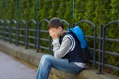 Schoolboy crying in the yard of the school royalty free stock image