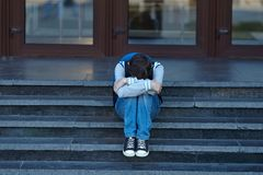 Schoolboy crying in the yard of the school. Negative emotion royalty free stock photo