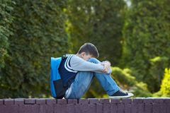 Schoolboy crying in the yard of the school stock images