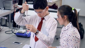 A schoolboy demonstrates how to add chemicals into a tube. stock video footage