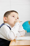 Schoolboy at desk looking up Royalty Free Stock Photography