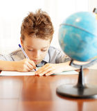 Schoolboy does house lessons Royalty Free Stock Photos