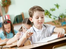 Schoolboy does some notes on the sheet of paper. Young schoolboy does some notes with pen on the sheet of paper royalty free stock image