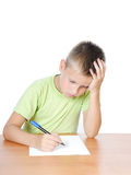 Schoolboy doing bored his homework. On white bacground royalty free stock image