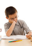 Schoolboy doing his homework. Schoolboy doing bored his homework - isolated royalty free stock photo