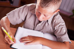 Schoolboy doing his homework Royalty Free Stock Photos