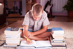 Schoolboy doing his homework. At his desk Royalty Free Stock Photo