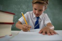 Schoolboy doing his homework in classroom. Attentive schoolboy doing his homework in classroom Stock Image