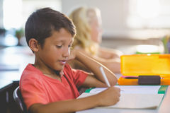 Schoolboy doing his homework. In classroom at school Stock Photography