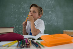 Schoolboy doing his homework in classroom. Thoughtful schoolboy doing his homework in classroom Royalty Free Stock Photos