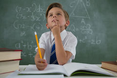 Schoolboy doing his homework in classroom. Thoughtful schoolboy doing his homework in classroom Stock Images