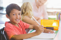 Schoolboy doing his homework. Portrait of schoolboy doing his homework in classroom at school Royalty Free Stock Photography