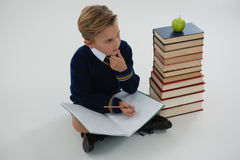 Schoolboy doing his homework while sitting beside books stack. Thoughtful schoolboy doing his homework while sitting beside books stack Stock Image