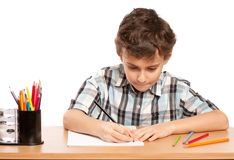 Schoolboy doing homework. Portrait of a schoolboy doing homework at his desk, isolated on white background Stock Photography