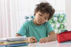 Schoolboy doing homework at his desk Royalty Free Stock Photography