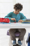 Schoolboy doing homework at his desk Stock Photography