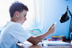 Schoolboy doing homework at home royalty free stock image
