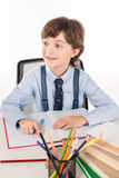Schoolboy doing homework. Schoolboy sitting at the table and doing homework isolated on white Stock Photos