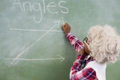Schoolboy doing mathematics on chalkboard in classroom Royalty Free Stock Photos