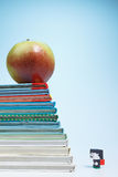 Schoolboy doll and an apple on books Stock Images