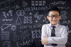 Schoolboy with doodle on the chalkboard Stock Image
