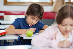 Schoolboy Drawing In Classroom Stock Photography