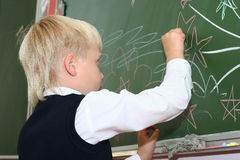 The schoolboy draws on a school board. The schoolboy draws a chalk on a school board Royalty Free Stock Image