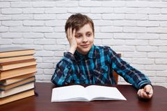 Schoolboy dreaming over empty note book. Elementary school, stud stock images