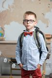 Schoolboy dressed in glasses and a backpack standing in the classroom stock photo