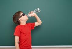 Schoolboy drink water from bottle near a blackboard, empty space, education concept Stock Images