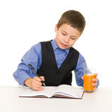 Schoolboy drinks juice at a desk with diary and pen Stock Photo