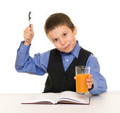Schoolboy drinks juice at a desk with diary and pen Royalty Free Stock Photos