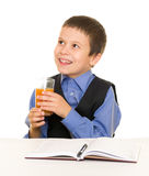 Schoolboy drinks juice at a desk with diary and pen Royalty Free Stock Photography