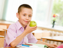 Schoolboy eating an apple Stock Photography