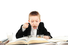 Schoolboy eats. Hungry schoolboy eating in the classroom Stock Photo