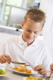 Schoolboy enjoying his lunch in a school cafeteria Stock Photos