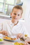 Schoolboy enjoying his lunch in a school cafeteria Stock Images