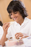 Schoolboy enjoying his lunch in a school cafeteria Stock Image