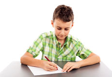 Schoolboy at exam. Writing at his desk, isolated on white background Royalty Free Stock Images