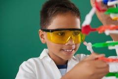 Schoolboy experimenting molecule model in laboratory Royalty Free Stock Photos
