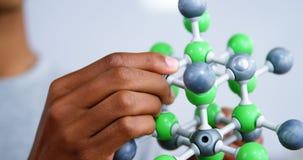 Schoolboy experimenting molecule model in laboratory at school