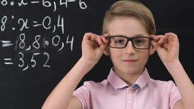 Schoolboy in eyeglasses looking at camera, math equation written on blackboard. Stock footage stock video footage