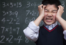 Schoolboy in front of blackboard with head in his hands Stock Photo