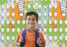 Schoolboy in front of light bulb graphics and orange and green paint Royalty Free Stock Photos