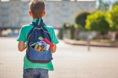 Schoolboy with full backpack go to school. Back view.  stock photo